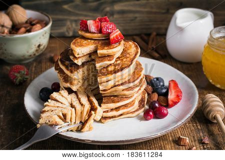 Healthy pancakes. Stack of delicious healthy whole grain pancakes with spelt flour served with strawberries, blueberries, cranberries, almonds and honey. Rustic style