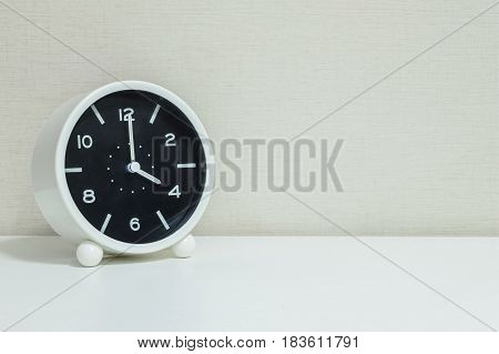Closeup black and white alarm clock for decorate in 4 o'clock on white wood desk and cream wallpaper textured background with copy space