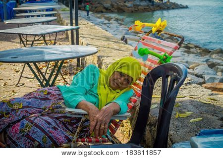 George Town, Malaysia - March 10, 2017: Close up view of unidentified old woman taking a nap in the waterfront esplanade