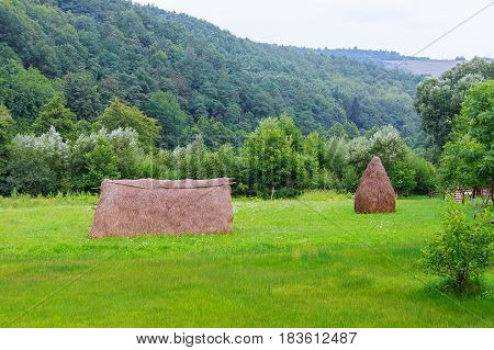 Haystack Near Orchard On Hillside. Agricultural Field In Mountain Area. Beautiful