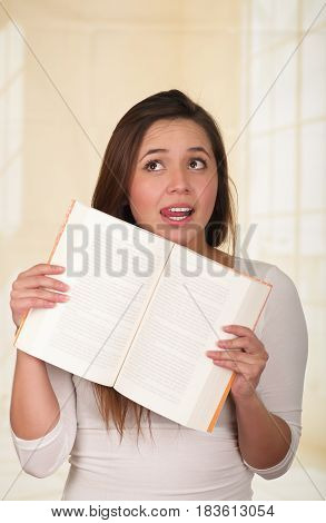 Young Pretty Woman holding an open Book and looking surprised.