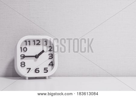 Closeup white clock for decorate show a quarter to two o'clock or 1:45 p.m. on white wood desk and cream wallpaper textured background in black and white tone with copy space