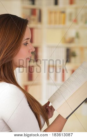 Young beautil and smart girl reading a book.