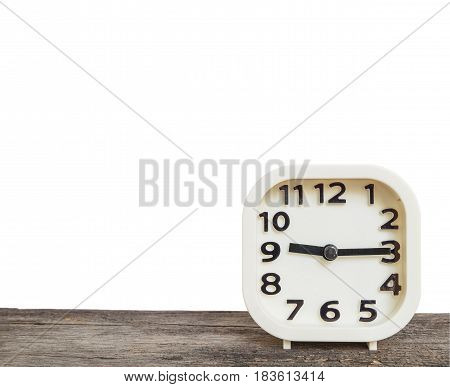 Closeup white clock for decorate show a quarter past nine o'clock or 9:15 a.m. on old brown wood desk isolated on white background with copy space