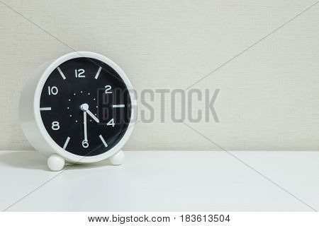 Closeup black and white alarm clock for decorate show show half past four o'clock or 4:30 p.m. on white wood desk and cream wallpaper textured background with copy space