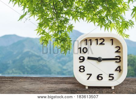 Closeup white clock for decorate show a quarter past nine o'clock or 9:15 a.m. on blurred mountain view background