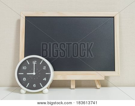 Closeup alarm clock for decorate show 9 o'clock with wood black board on white wood desk and cream wallpaper textured background selective focus at the clock