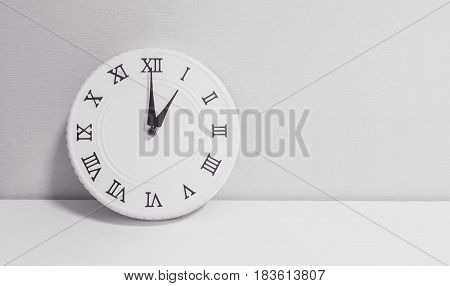 Closeup white clock for decorate in 1 o'clock on white wood desk and wallpaper textured background in black and white tone with copy space