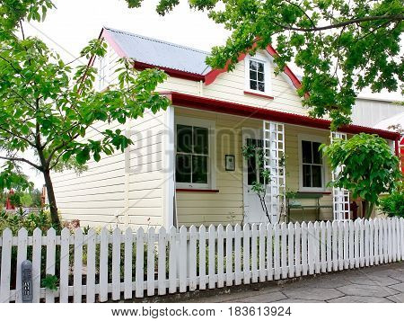 Weatherboard pioneer cottage with verandah and dormer window