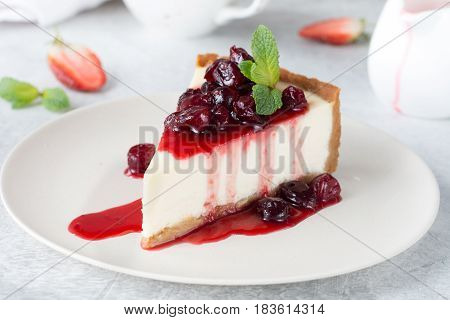 Slice of plain cheesecake with cranberry sauce on white plate decorated with mint leaf. Closeup view