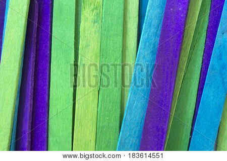 This is a photograph of Blue, Green and Purple colored popsicle sticks background