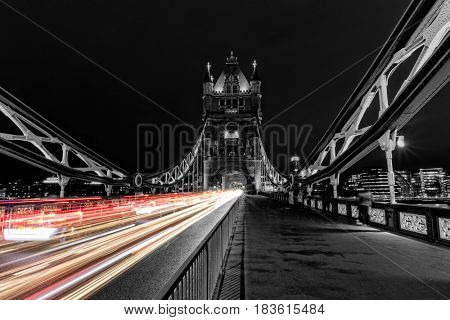 Tower Bridge in London in black and white, UK at night with blur colored car lights. One of the most famous history building in England