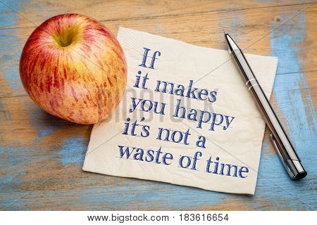 If it makes you happy it is not a waste of time - inspirational handwriting on a napkin with a fresh apple