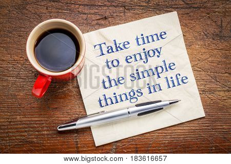 Take time to enjoy the simple things in life - inspirational handwriting on a napkin with a cup of coffee