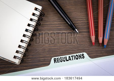 Regulations Concept.  Folder Register on a dark wooden desk.