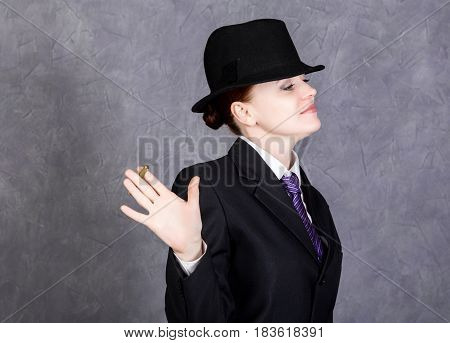 Young woman in manly style with mini cigar on gray background, girl in man's suit and tie, white shirt and hat. black and white