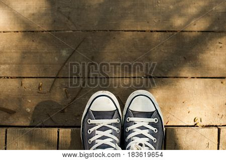 Denim sneakers on wooden boards with free space for text.
