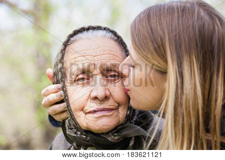 Picture of a beautiful young woman kissing her sick grandmother