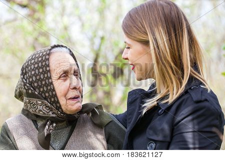 Picture of a beautiful woman spending time with her sick grandmother outdoor