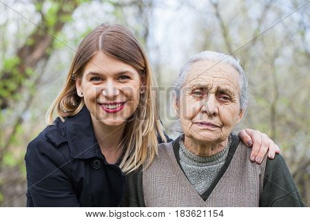 Picture of an elderly woman with her kind young carer outdoor during springtime
