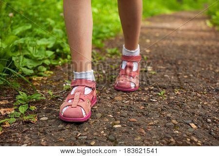 little girl legs in pink sandals walking on stony forest path