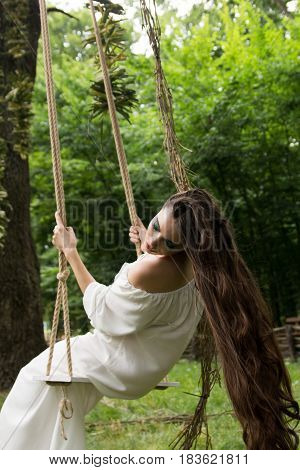 Young beautiful girl with long hair in white dress is riding rope swing in forest. Folk style.