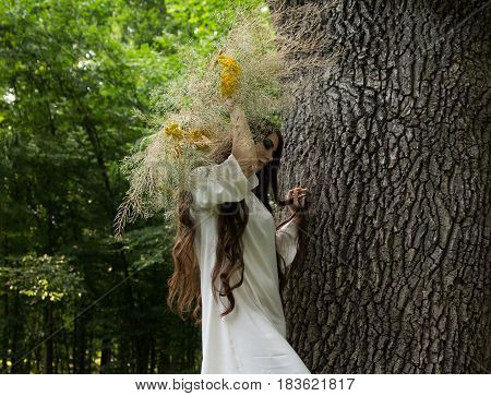 Young beautiful girl in wreath walks in forest. Folk style.
