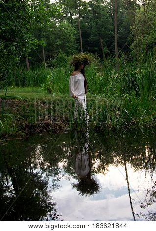 Young beautiful girl in wreath dips into water at folk festival