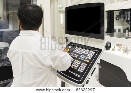 The CNC panel with the operator.The CNC machine operation by CNC operator with the manual book.