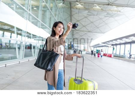 Woman taking photo by camera with her luggage in airport
