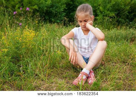 Girl In White T-shirt And Jeans Shorts Sits Lost In Thought On The Grass
