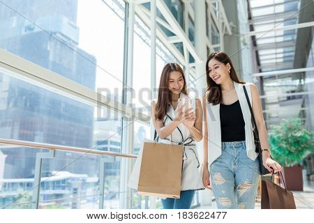 Friends go shopping together and using cellphone in shopping mall