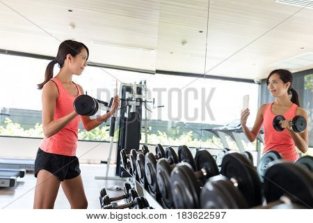 Woman practices lifting weights in gym and taking selfie