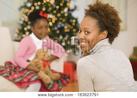 African mother taking picture of daughter at Christmas