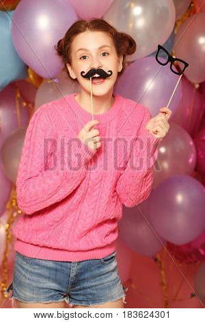 Party concept: happy girl with  fake mustaches and glasses.