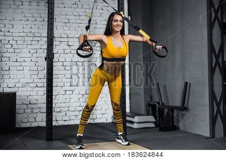 Training in the gym. Fitness girl to build up muscles. Fitness trainer to warm up.