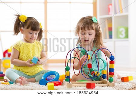 Children playing with toys in kindergarten or home