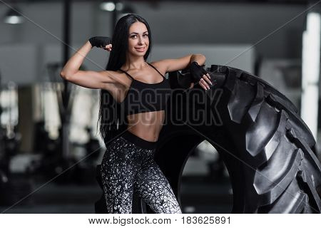 Concept: power strength healthy lifestyle sport. Powerful attractive muscular girl engaged in cross fit training with giant tires in the gym. Sportswoman posing after a hard workout