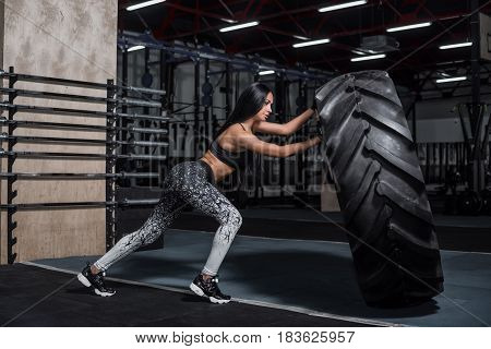 Powerful attractive muscular girl engaged in cross fit training with giant tires in the gym. The athlete pushes a large wheel. Exercise with heavy weight in the gym.