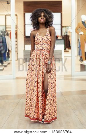 Pretty tall afro-american woman in a long dress and with curly hair standing in a shopping mall.