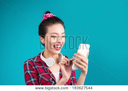 Happy young asian woman using smartphone standing over blue.