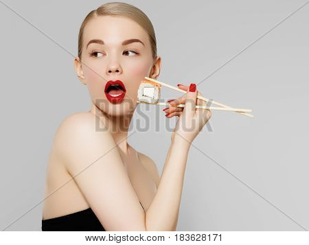 Beautiful Blonde Girl With Red Lips And Manicured Nails Eating Sushi, Healthy Japanese Food. Beautif