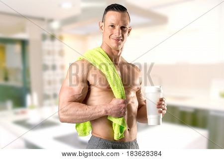 Powerful athletic man with great physique holding a gym bottle