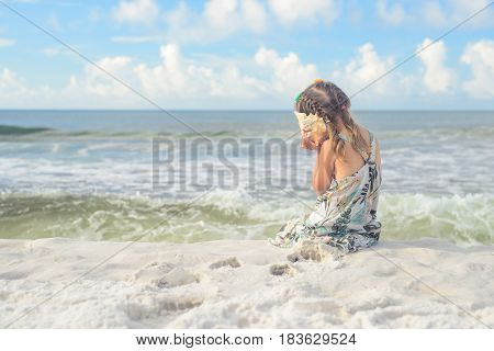 Girl sitting on sand at beach near water, playing with big seashell - if you listen long enough, you can hear sounds of the ocean.