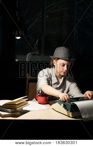 Portrait of a girl in a hat sitting at a table with a typewriter and books making notes at night