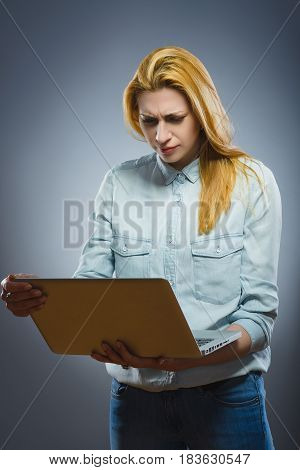 Young business woman disgusted by the content on her laptop.