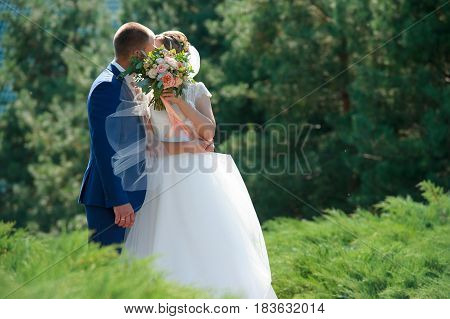 Bride and groom embarrassed and covered their faces with a wedding bouquet. Wedding of two creative people.