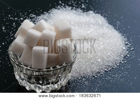 white refined sugar and granulated sugar close up on black background