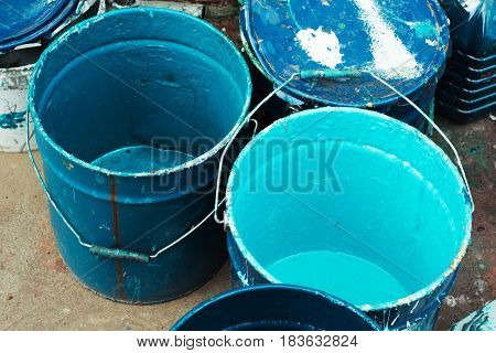 Paint dirty bucket with blue color on asphalt with paintbrush.Old paint in messy rusty cans ready for recycling.