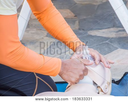 cpr training chest compression dummy basic life support selective focus of hand and face mask